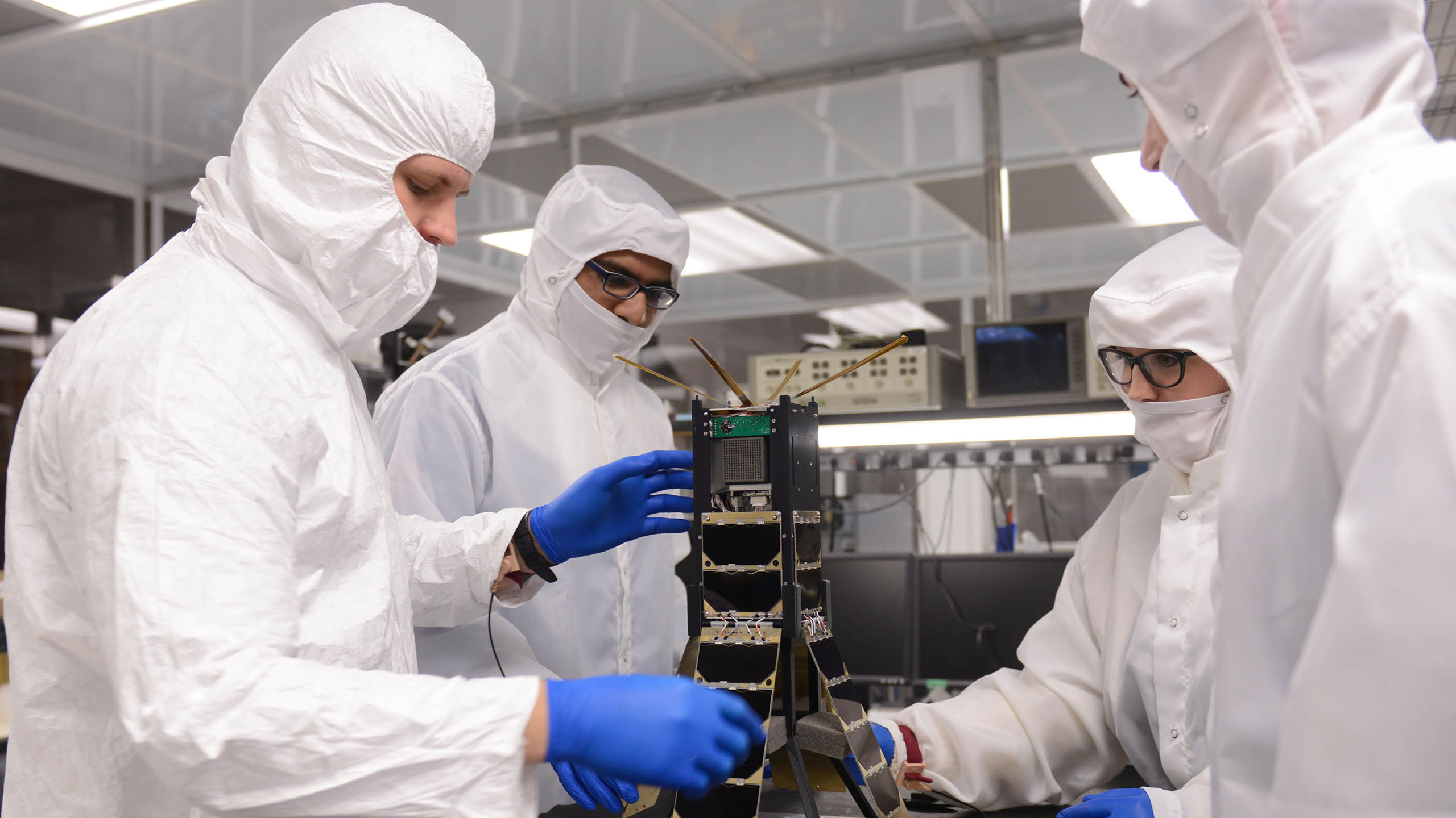Students building a small satellite in a clean room.