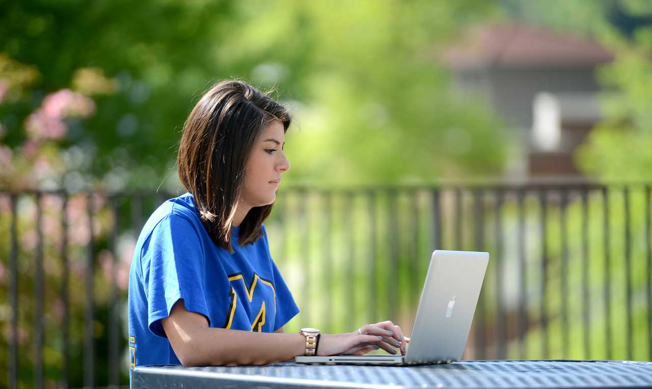 A student working on a laptop.
