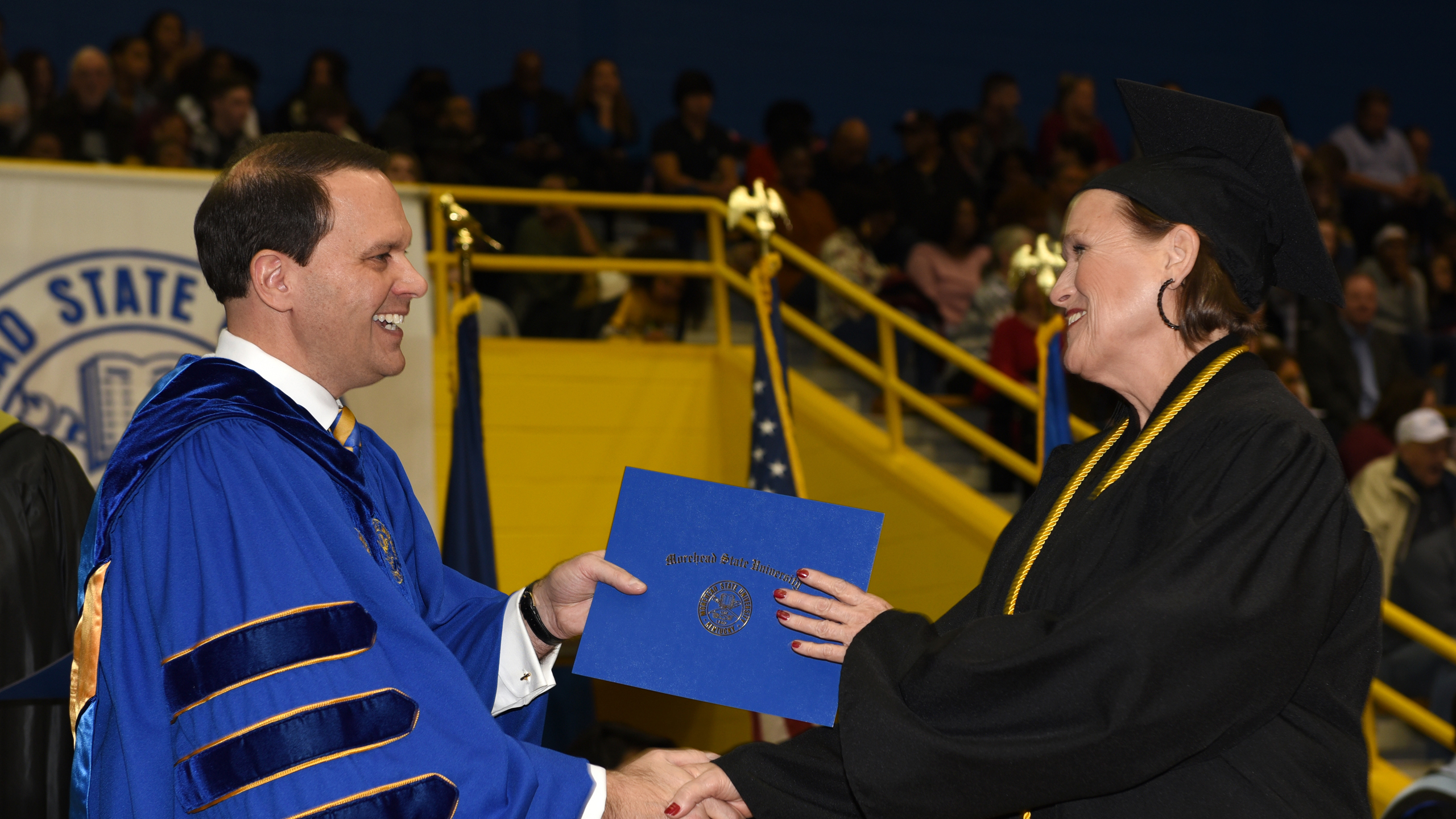 A student receives her diploma from MSU President Jay Morgan