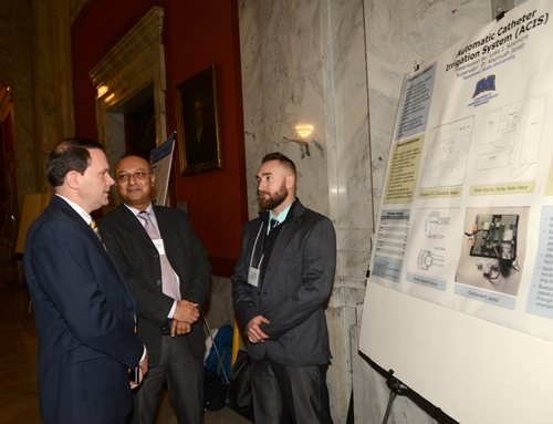 Dr. Morgan talks with a student and faculty member at Posters-at-the-Capitol.