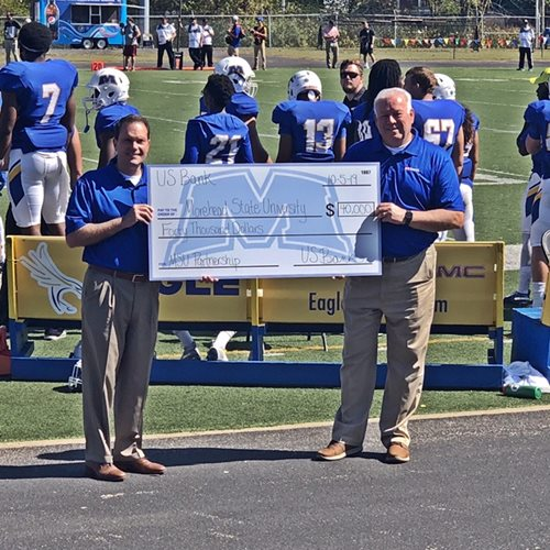 Dr. Morgan receives a donation from US Bank at half-time during an Eagle Football game.