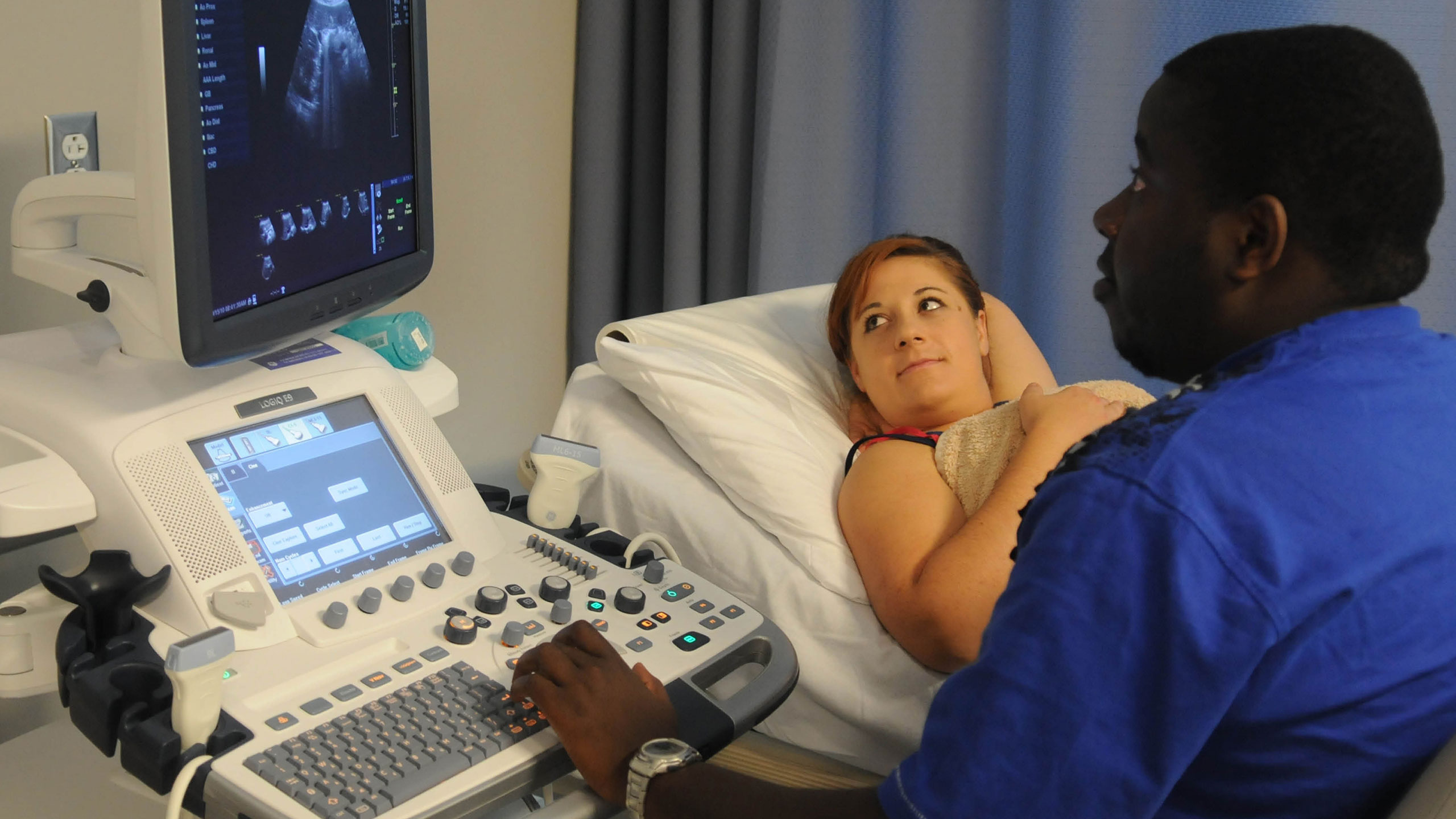 A student conducting a sonogram on a patient.