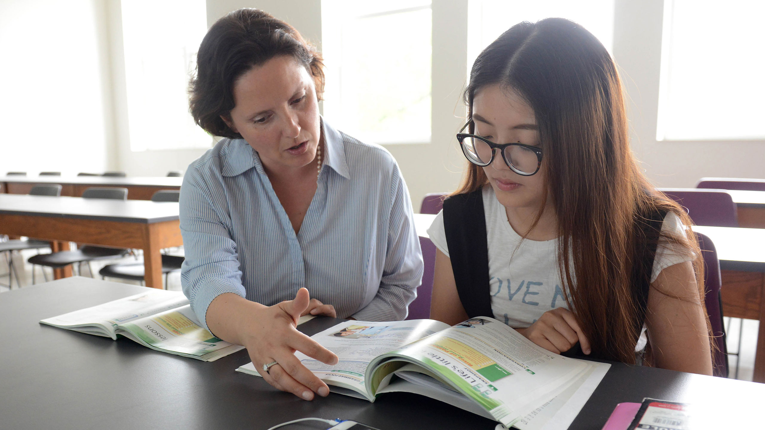 A student and an instructor reviewing a book.
